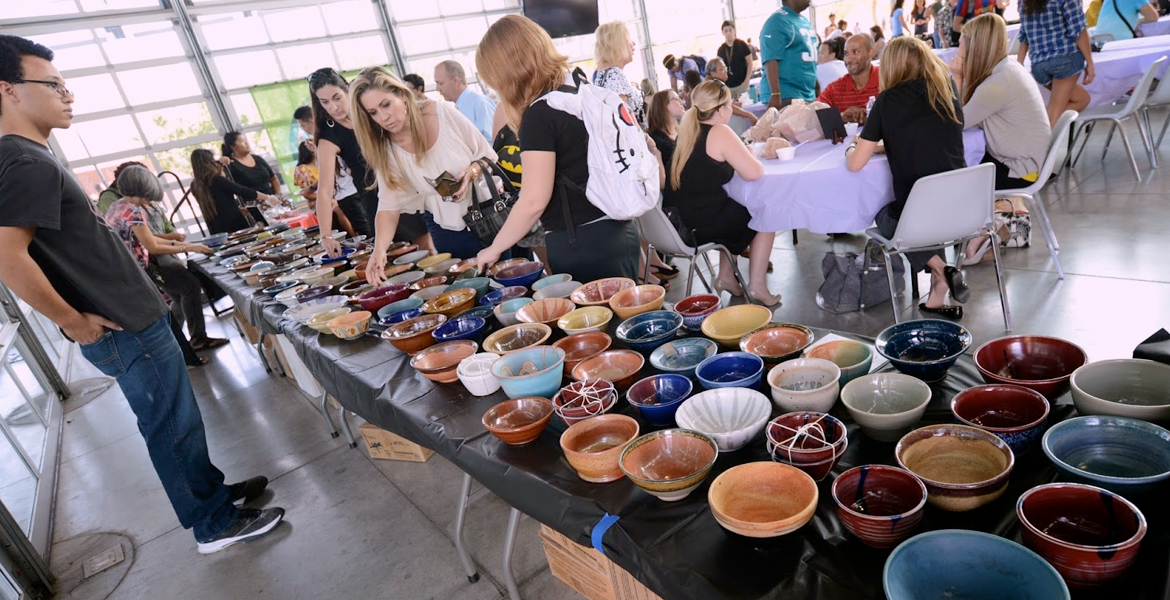 People looking at different bowls on a table to purchase